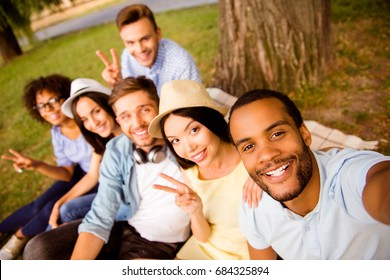 Selfie time! Six international students with beaming smiles are posing for selfie shot, that african handsome guy is taking, outside school building. Gathered, cheerful, smart and successful youth