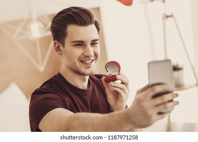 Selfie time. Smiling excited man feeling nervous while making selfie with expensive wedding ring for his sweetheart