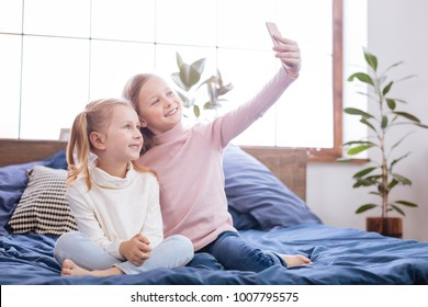 Selfie time. Sweet alert blond sisters smiling and taking pictures on their phone while sitting on the bed
