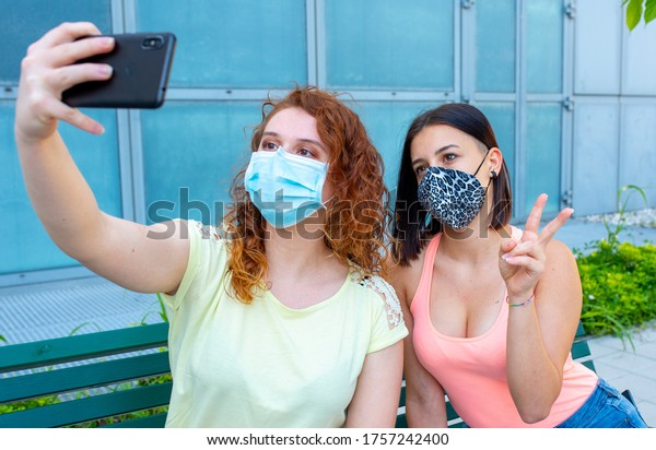 selfie time of two beautiful girls sitting on a bench in the city, taking pictures with their mobile phone while maintaining the rules of prevention and use of the protective mask, the new normality