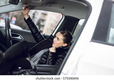 Selfie time. Woman taking a selfie in her car. Beautiful smiling woman taking a photo in her automobile.