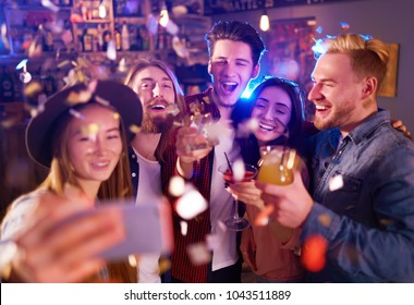 Selfie Time. Young Group of Friends Partying In A Nightclub And Toasting Drinks. Happy Young People With Cocktails At Pub. The People Have A Great Mood And They Smile A Lot.