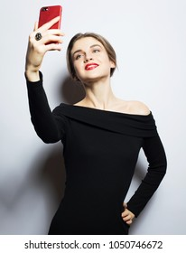 Selfie time. Young smiling blond woman doing selfie on  white background.