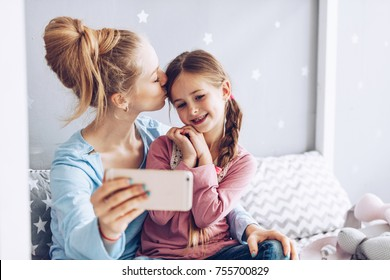 Selfie together. Mom and daughter mkes photo  on smartphone at home