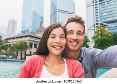 Selfie travel photo with phone of young adults tourists in love smiling at camera. Interracial couple in Hong Kong city, urban living. Asian multiracial chinese woman, Caucasian man in their 20s.