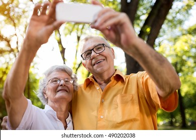 Selfie of two happy pensioner with smartphone, senior couple in love