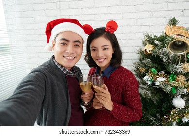 Selfie of two young Asian office workers posing with wine glasses in Christmas time