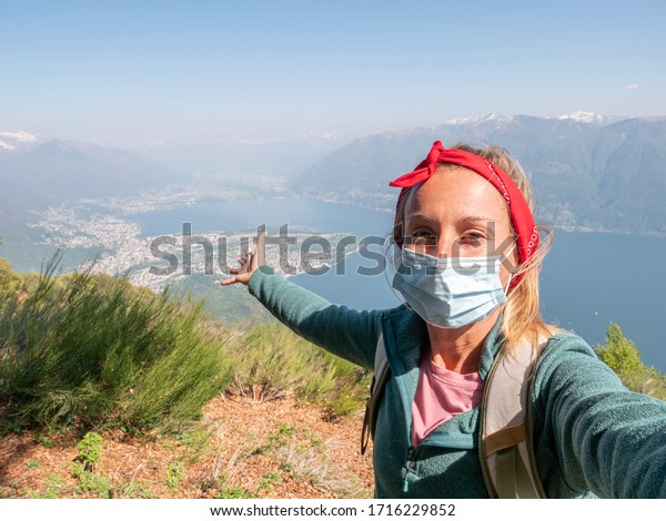 Selfie of woman hiking outdoor wearing a medical face mask to prevent COVID-19 and social distancing from people. Female with facial mask hiking enjoying nature, coronavirus pandemic protection