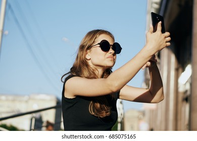 Selfie, woman taking pictures on phone on building background