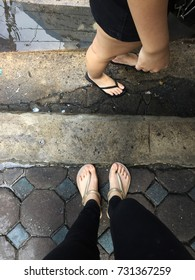 Selfie Woman's Feet Wearing Sandals and Black Jeans on Tile Background Great For Any Use.