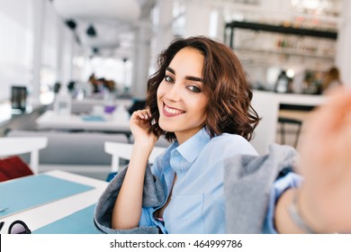 7a1e1994457ac Selfie-portrait of cute brunette girl with short hair sitting at table in  gray plaid