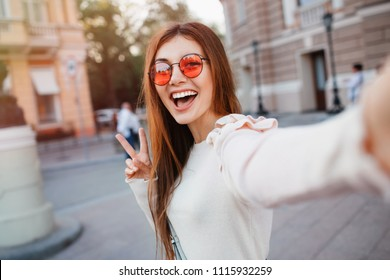 Selfie-portrait of pretty girl with long brunette hair at street background. wears beige dress, red sunglasses, make up. Smiling and positive.young woman in glasses making selfie , showing two fingers
