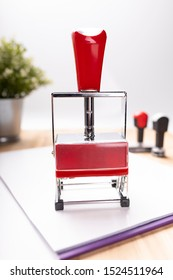 A self-inking, rubber date stamp. Paperwork. A composition of office accessories.