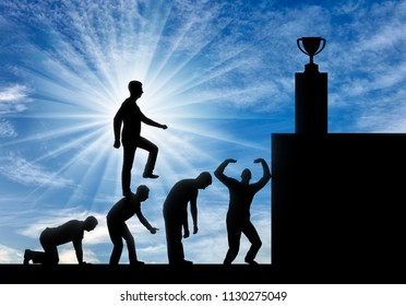 A selfish man walks on the heads of people as on the steps to his goal. Conceptual scene of a narcissistic and selfish businessman