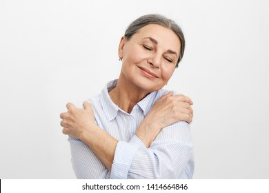 Self-love, joy and happiness concept. Portrait of happy joyful elderly mature lady with wrinkled skin and gray hair posing in studio, dressed in blue shirt, closing eyes and embracing herself