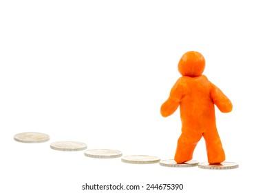 Self-made human plasticine figure following a trail of money.