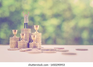 Self-made millionaire / become a billionaire from nothing, story of successful leader concept : Business tycoon raise hand to show dignity, 4 or four golden trophy cup of winner on rows of rising coin