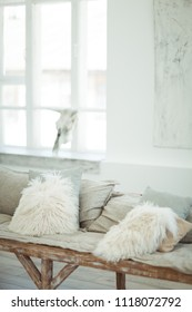 A self-made sofa with light soft pillows in a light-white interior