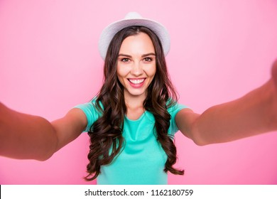Self-portrait of adorable attractive nice charming amazed curly-haired brunette young smiling girl wearing sunhat. Isolated over pink pastel background