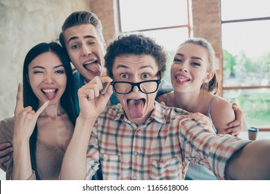 Self-portrait of four cheerful glad people, guys and girls having rest, pause, break at work, fooling, grimacing, showing tongue out, asian girl showing horn, diversity, meeting, gathering