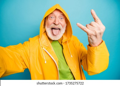 Self-portrait of his he nice cheerful cheery crazy naughty grey-haired man wearing yellow topcoat having fun showing horn symbol party isolated on bright vivid shine vibrant blue color background