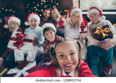 Self-portrait of large family gathering. Grey-haired grandparents, granddaughter, grandson, grandchildren, brother, sister holding, keeping, getting gifts, navidad