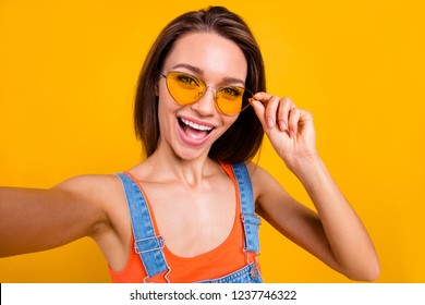 Self-portrait of nice cool lovely dreamy adorable attractive cheerful positive lady touching glasses having fun opened mouth isolated over bright vivid shine yellow background