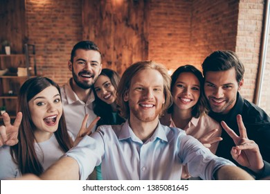 Self-portrait of nice cute attractive lovely charming cheerful cheery glad positive ladies gentlemen having fun showing v-sign dream in industrial loft interior room indoors