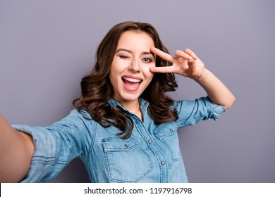 Self-portrait of nice cute cheerful lovely attractive magnificent brunette girl with wavy hair in casual denim shirt, opened mouth, showing v-sign near eye, isolated over grey background