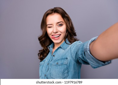 Self-portrait of nice cute flirty cheerful lovely attractive adorable magnificent brunette girl with wavy hair in casual denim shirt, showing tongue out, winking, isolated over grey background