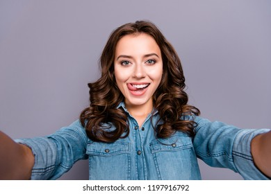 Self-portrait of nice cute stylish trendy flirty cheerful lovely attractive adorable brunette girl with wavy hair in casual denim shirt, showing tongue out, isolated over grey background