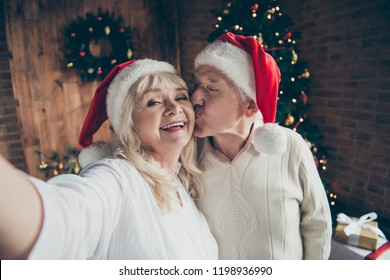 Self-portrait of two funny flirty cheerful positive beautiful charming adorable grey-haired people spouses in hats with white balls near decorated fir pine tree granddad kissing grandma