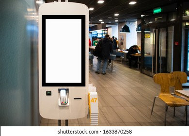 Self-service desk with touch screen and payment terminal in fast food restaurant
