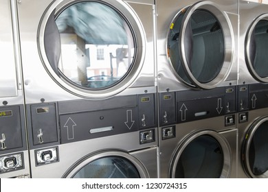 self-service laundry facilities concept - washing machines with clothes inside at laundromat