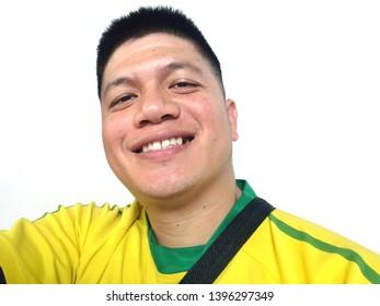 Selfy thai man wear yellow and green t-shirt and smiling on white background at Samai, Bangkok, Thailand, 12 May 2019.