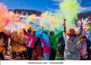 "Seli, Greece - February 17, 2019: Crowds of unidentified people throw colour powderduring the annual winter event ""Day of Colours"" in the snowy landscape"