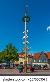 Seligenstadt, Germany - May 2010: Full view of the maypole (Maibaum) erected on the marketplace on a nice day with blue sky. The decorated tree trunk is a tradition going back to the 16th century.