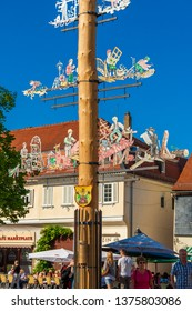 Seligenstadt, Germany - May 2010: Great close-up view of a maypole or Maibaum, a tall wooden pole erected on the marketplace. The pole is decorated with emblems depicting local crafts and industry.