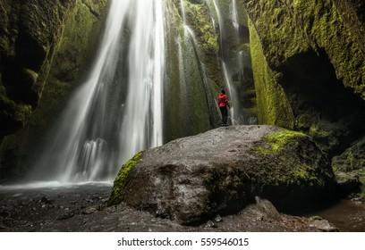 Seljalandsfoss, Iceland - Lone person on large rock inside Gljufrafoss cave waterfall