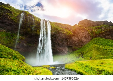 Seljalandsfoss waterfall in Iceland at sunset. Beautiful summer landscape. Famous travel destinaation