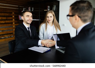 Sell concept. Young couple greetings with manager in office.