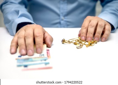 Sell gold jewellry, pawnbroker with euro banknots in the hand, sale and buying