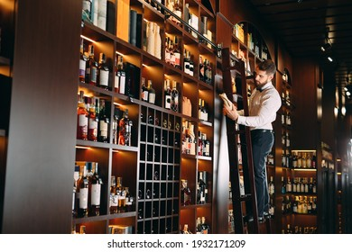 The seller of alcoholic beverages sorts bottles standing on the ladder
