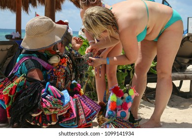 Seller and buyers on a tropical beach.