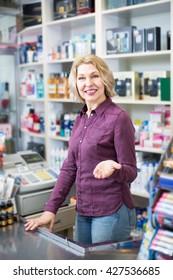 seller at cash register desk in cosmetic shop