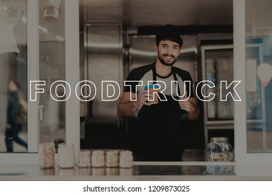 The Seller With Coffee Stands In The Food Truck. Black Beard. Ready To Work. Waiting For Clients. Fast Eating Place. Service Personal. Opened Window. Apron Work Uniform. Sunny Day.