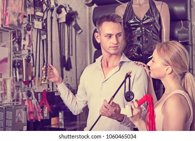 Seller consulting customer with assortment of adult products in the store