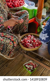 The seller is cutting water guava for making traditional food rujak at a busy street food market