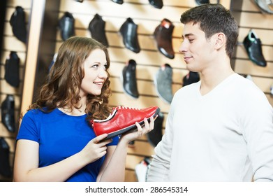 seller female assistant demonstrate shoes to young man during footwear shopping at shoe shop