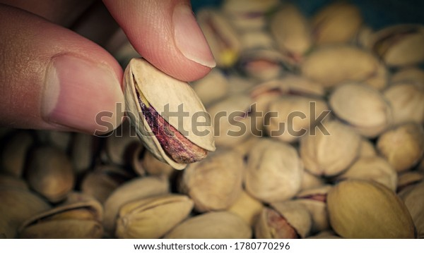 Seller fingers is holding one of Pistachios over the full surface of it.